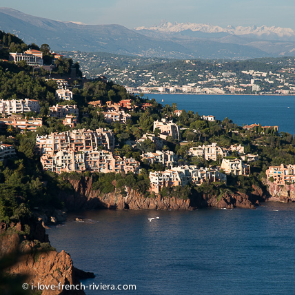 The red mountains of the Esterel dive directly into the sea. Here on the road to the Corniche d'Or, from La Napoule to Saint-Raphael. At the bottom of the Gulf, we can see La Napoule and the snowy Alps